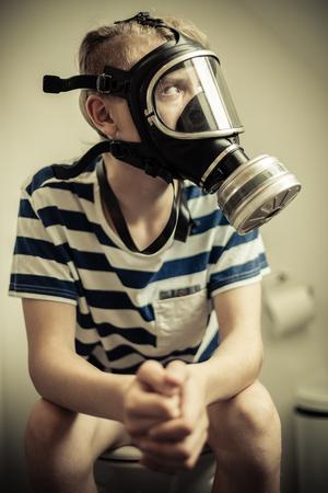 よそ見防毒マスクを身に着けているズボンとトイレの便座に座っているティーンエイ ジャーの男の子