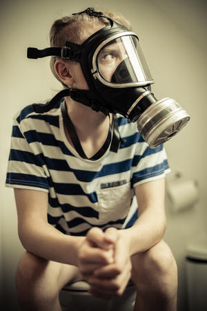 constipated: Teenager boy sitting on toilet seat with pants off wearing gas mask, looking away