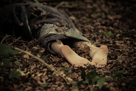 Close up view of bare feet sticking out of bag with corpse thrown in woods strewn with withered foliage