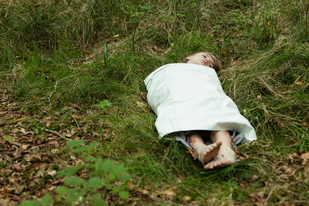 Dead body of teenager with blond hair wrapped in white paper with feet and head sticking out laying face up in grass