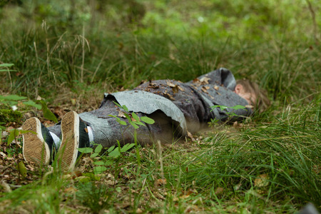 Low angle view of dead young boy wrapped in black plastic fabric laying face down in green grass covered with withered leaves