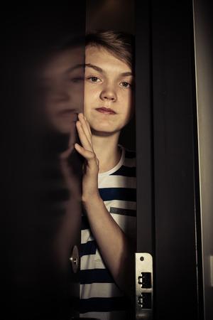 Großaufnahme des emotionslosen Jungen in abgestreiftem T-Shirt, das heraus durch schwarze angelehnte Tür schaut Standard-Bild