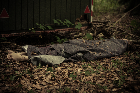 Corpse wrapped in dark plastic fabric or rug laying stretched on the ground strewn with leaves near metal container Stock Photo