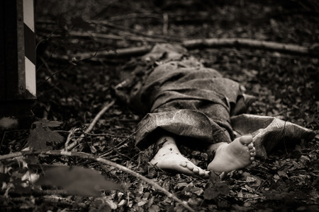 murdered: Close up view of bare feet of dead body sticking out of bag or rug, thrown in woods Stock Photo