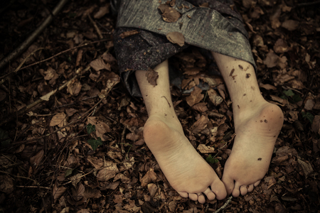 Close up view of wrapped up corpse bare feet laying on ground face down covered with withered foliage