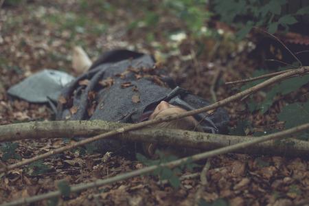 緑豊かな森林のシートの下で横になっている覆いを取られた頭部で殺人事件の被害者の体 写真素材