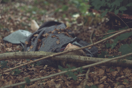 Body of murder victim with uncovered head lying under sheets in leafy forest