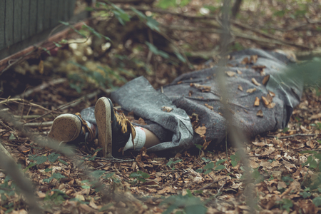 Murder victim wrapped in tarpaulin with feet protruding in leafy forest Stock Photo - 71650611