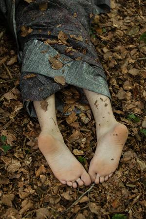 Verlassene Körper des Mordopfers mit barfuss aus Plane Blatt vorstehenden Körper auf grünen Boden bedeckt Standard-Bild - 71564592