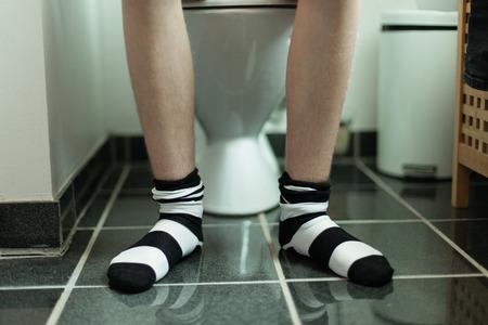 トイレに座っていた縞の靴下を身に着けている若い男の子の足 写真素材