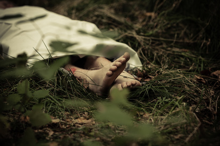 Lower body of abandoned murder victim in dark countryside with barefeet protruding Stock fotó