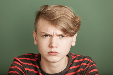 Petulant young teenage boy with a fierce scowl glaring at the camera with an intense stare Stock Photo