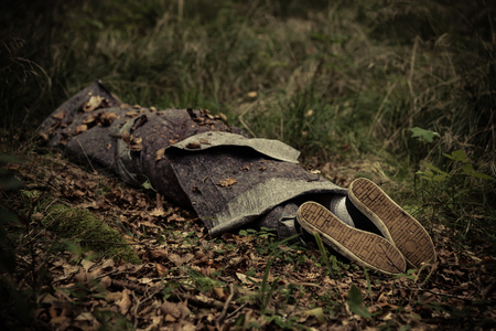 gruesome: Body of murder victim hidden in autumn forest wrapped in tarpaulin sheets Stock Photo