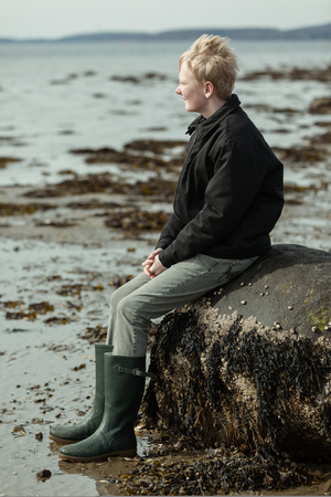 Single teenage boy in blond hair sitting on old rock at cold, windy beach during low tide