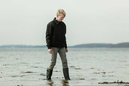 Teen youth dressed in black jacket, gray pants and rubber boots stepping in water during high tide Stock Photo