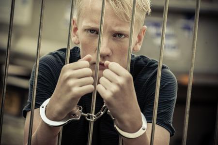 Opstandige tiener werd gevangen genomen door de politie, die op de camera stond van achter de tralies met handboeien handen aan de camera staan