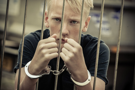 Rebellious teenager taken prisoner by the police standing glaring at the camera from behind bars with handcuffed hands