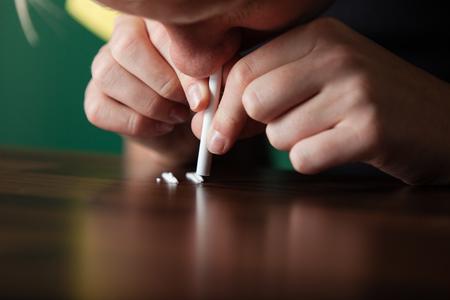 薬物乱用の概念の彼の鼻孔に snort にストローを使用してテーブルの行で広げて結晶コカインのスニッフィング中毒少年