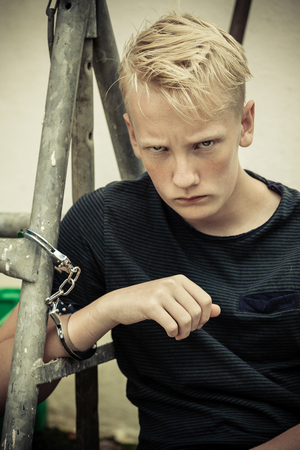 glowering: Rebellious angry teenage boy in handcuffs chained to a metal railing or fence glaring at the camera with an intense expression
