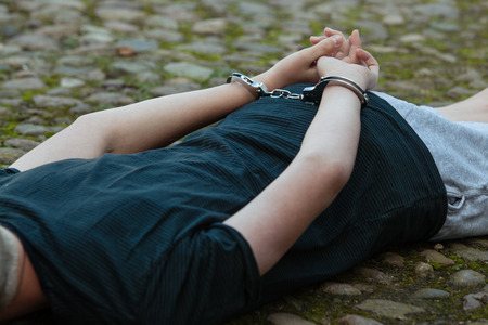 Young boy being arrested by the police lying on cobblestones outdoors with his hands cuffed behind his back in handcuffs, close up torso view
