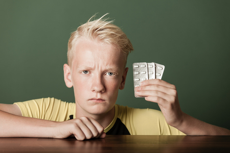 Scowling teenage boy holding up pills sealed in blister packs in his hand as he leans on a wooden table with an intense stare