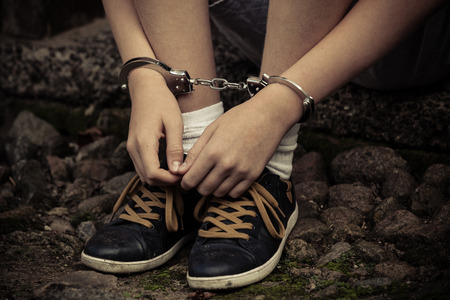 Young boy in handcuffs and sneakers sitting with his hands resting on his shoes on old cobblestones after being arrested, close up view of the manacles