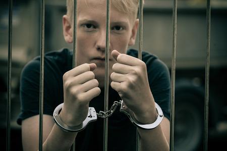 Kajdanki nastolatka za kratkami w celi więziennej wpatrując się uważnie w kamerę bez skrupułów jego zachowanie przestępcze