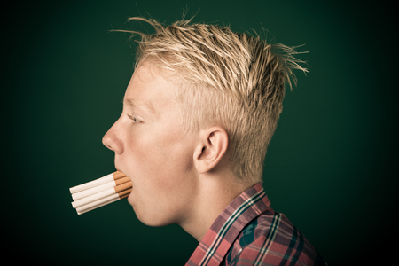 Young boy with a mouthful of cigarettes in a concept about the dangers of smoking and tobacco, close up profile view