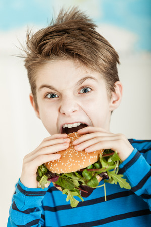 Young boy biting into a salad burger with fresh rocket leaves on a sesame bun with a look of surprise and determination