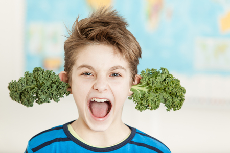 Young boy sprouting fresh kale leaves from his ears yelling at the camera in a spoof on the concept of a healthy diet and nutrition