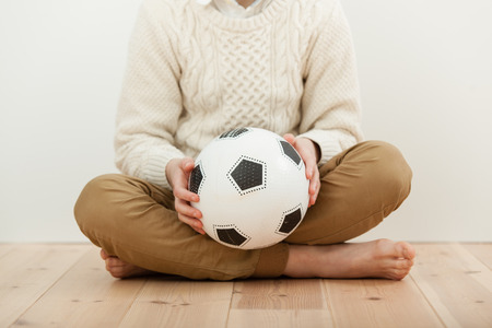 trouser legs: Barefoot cross-legged boy sitting on a wooden floor holding a soccer ball in his hands, cropped view without head
