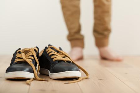 Paar saubere schnüren sich oben Turnschuhe auf einem Holzboden mit den unscharfen Beine eines barfuß Junge im Hintergrund Standard-Bild - 71691936