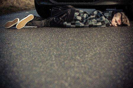 fatality: Motor vehicle accident and fatality concept with a young bloodied teenage boy lying under the front wheels of a car on a tarmac road with foreground copy space Stock Photo
