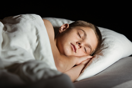 Boy with eyes closed asleep in bed. Both hands are together between cheek and pillow.