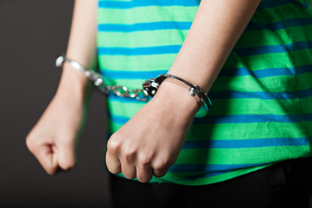Close up on pair of hands from child or teenager in green and blue shirt tied with metal handcuffs Stockfoto