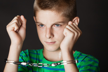 Single teenaged boy with both arms up near face while chained in handcuffs while grinning