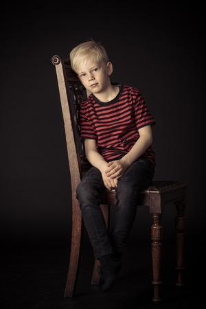 Calm thoughtful little blond boy sitting on an old wooden kitchen chair in the shadows looking thoughtfully at the camera in a full length view