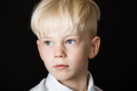 잠겨있는 잘 생긴 작은 금발 소년 쳐다 조심스럽게 어두운 배경에 샷 머리 위로 닫습니다.