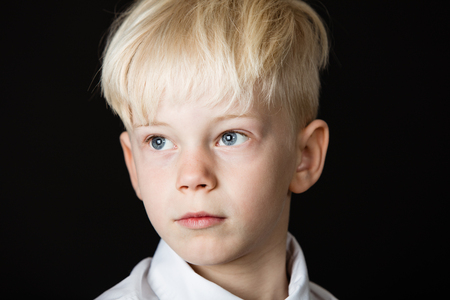 Pensive handsome little blond boy staring thoughtfully off to the side in a close up head shot on a dark background