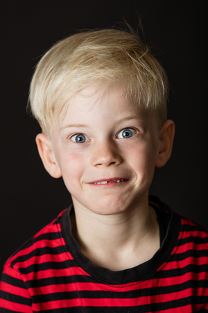 Cute wide eyed little blond boy with a missing front tooth pulling a funny face for the camera over a dark background