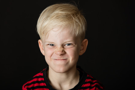 fiercely: Angry frustrated little blond boy screwing up his face in a grimace as he stares fiercely at the camera over a dark background Stock Photo