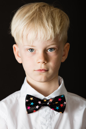 Handsome little blond boy in a formal white shirt and smart bow tie decorated with colorful stars on black looking directly at the camera in a close up head shot Stock Photo