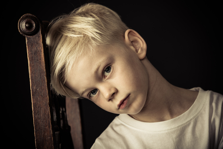 Thoughtful little blond boy sitting on an old wooden kitchen chair tilting his head against the backrest as he stares at the camera Archivio Fotografico