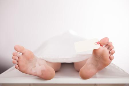 Boys body or cadaver lying on a mortuary slab covered with a white sheet with a blank tag tied to his toe awaiting identification, view from the bare feet