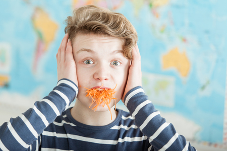 Single overwhelmed boy with hands on ears and mouth full of carrot shreds while standing in front of map indoors Stock Photo
