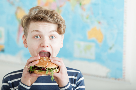 Single cute teenage boy in blue and white striped shirt eating a burger with an excited expression in front of map