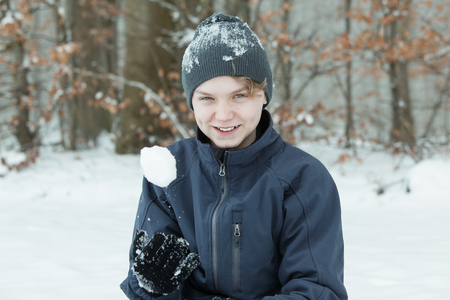 Single boy in hat and jacket with zippers playing with snowball outside with trees and brown leaves behind him.