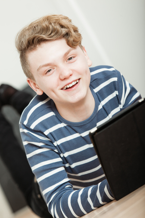 Smiling handsome boy in long sleeve blue and white shirt laying on floor looking at tablet computer inside dark case Stock Photo