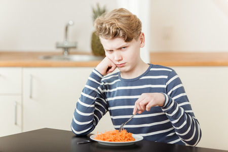 Pouting boy in long sleeve shirt and wavy hair sitting in front of shredded carrots at table in kitchen