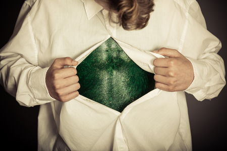 Boy opening shirt to reveal bizarre lizard skin for concept about science fiction alien transformations